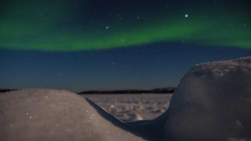 Une aurore boréale traverse le ciel derrière une motte de neige en avant-plan.