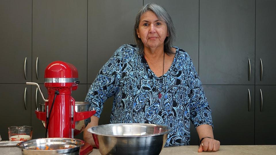 Jeannette Boivin, dans une cuisine, prépare des gâteaux pour une activité de la communauté
