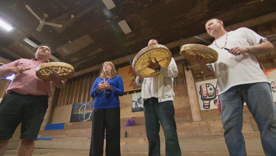 Une femme est entourée d'hommes qui jouent du tambour traditionnel autochtone.