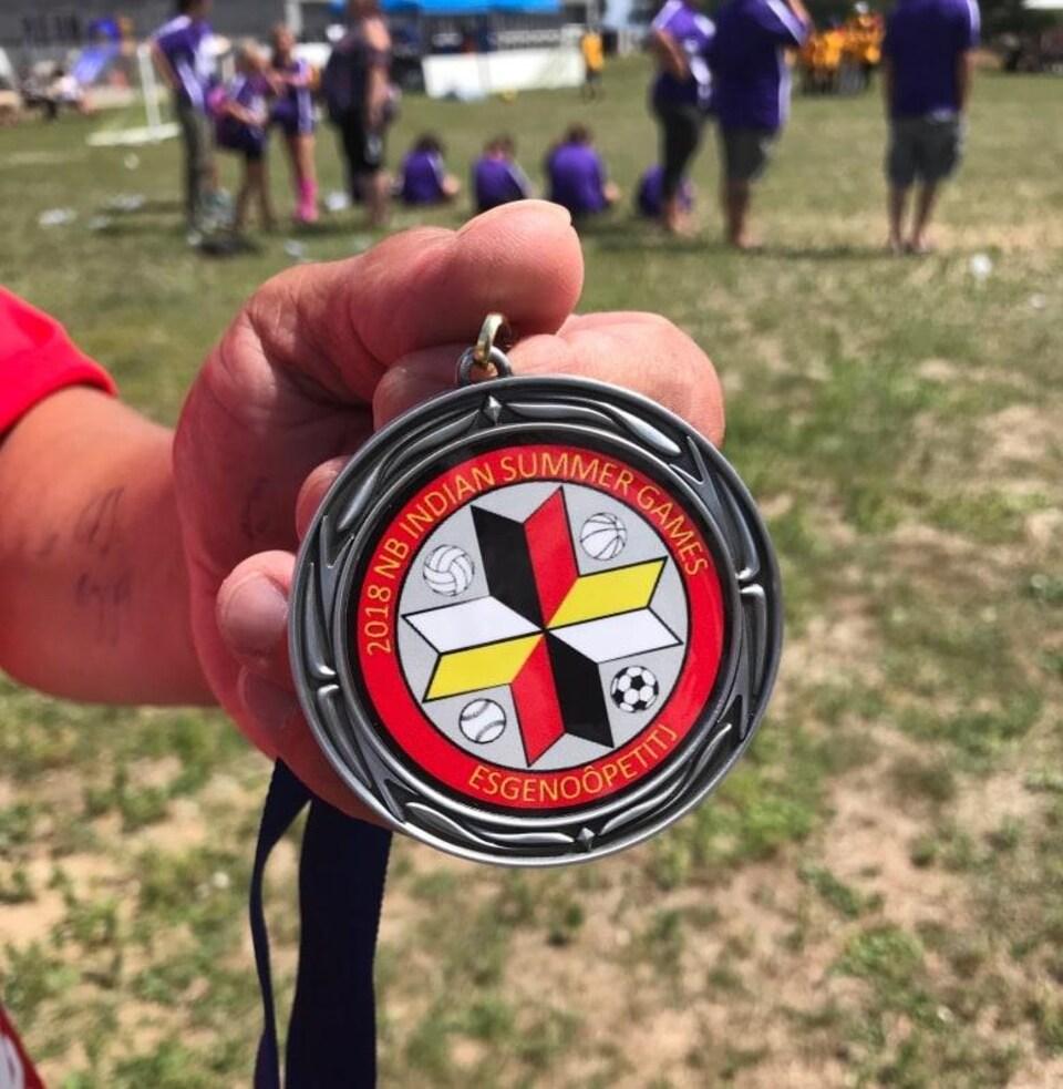 Un homme tient une médaille des Jeux autochtones d'été du Nouveau-Brunswick.