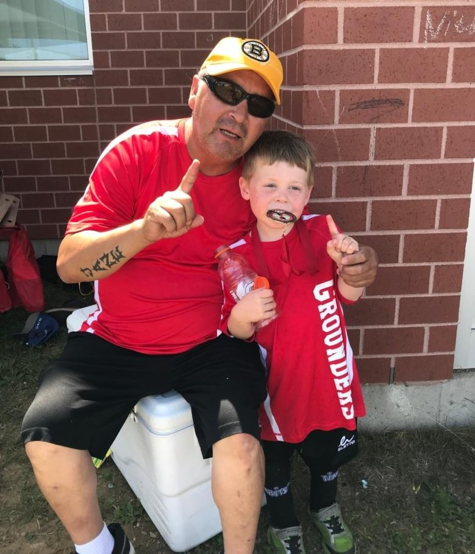 Un homme autochtone et un enfant vêtus de rouge s'enlacent.