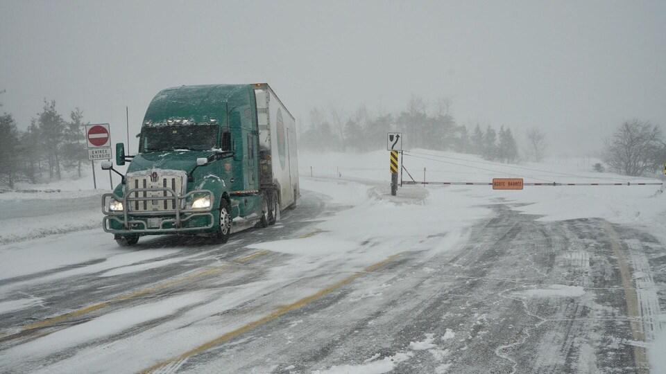 Un poids lourd circule à proximité d'une route fermée en raison d'une tempête de neige.