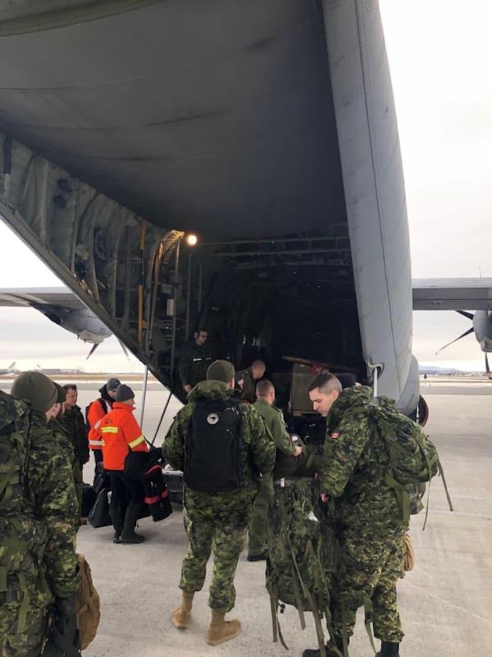Un groupe de militaires en uniforme embarquent à bord de l'avion.