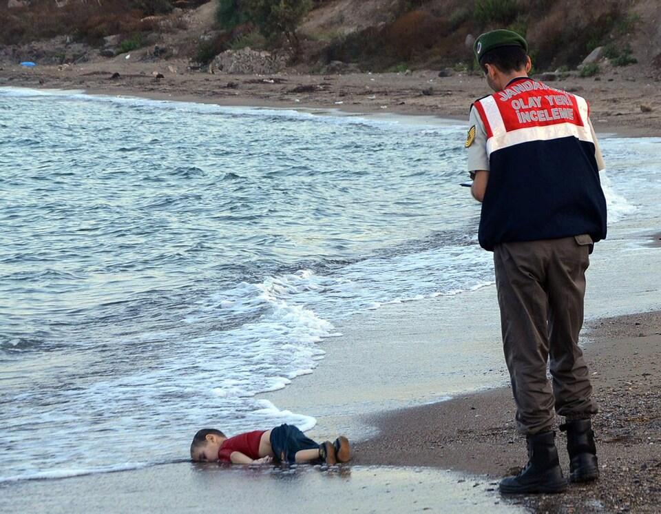 Un policier devant le corps d'Aylan Kurdi, un syrien de 3 ans, sur une plage turque