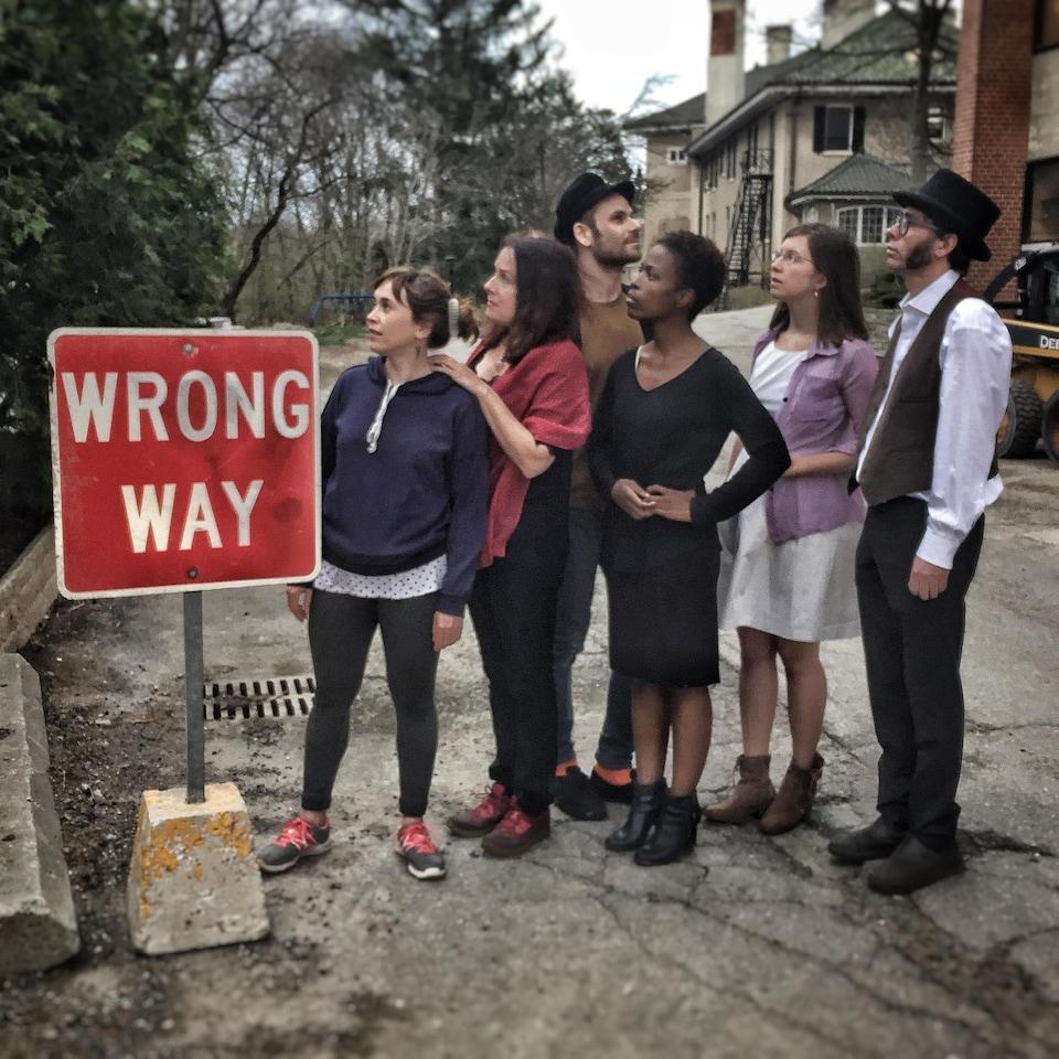 5 acteurs regardent dans une même direction alors qu'un autre regarde dans le sens opposé. Sur un panneau d'affichage est inscrit en anglais : Wrong Way, mauvaise direction en français.