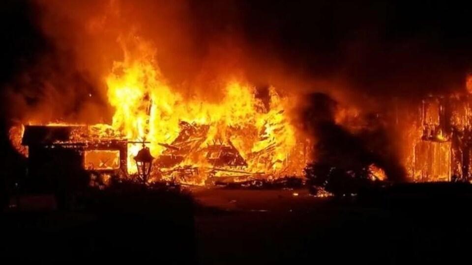 Un pompier passe devant les ruines en flammes