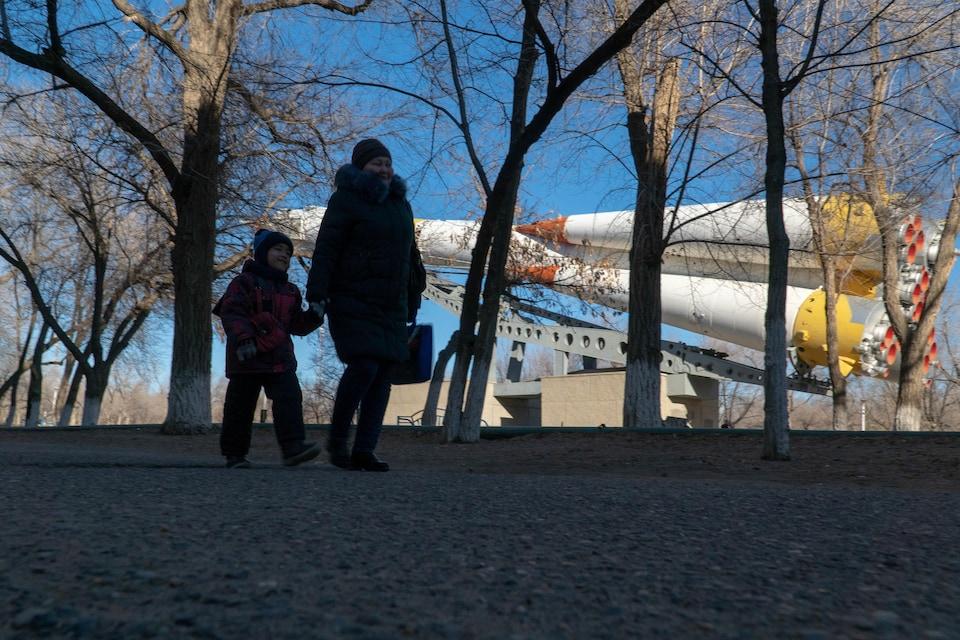 Une mère et son enfant marchent dans l'une des places de la ville.
