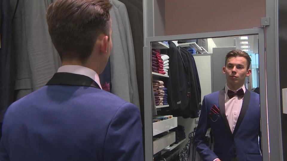 Un garçon se regarde dans le miroir.