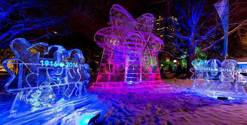 On peut voir sur cette image trois sculptures de glace illuminées en bleu et rose lors du Bal de neige de 2016.