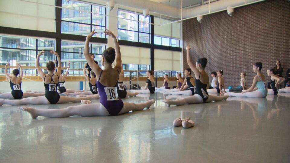 Les ballerines sont en position grand écart au sol pour démontrer leur flexibilité aux juges lors de leur audition.
