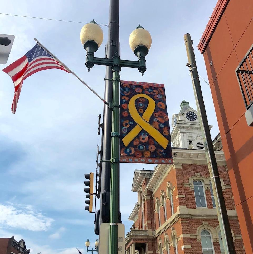 Une banderole de Passion Works et un drapeau américain sont accrochés à un lampadaire au centre-ville d'Athens devant un immeuble en briques rouges.