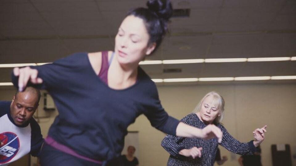 Trois danseurs en pleine action, dans la même position, les bras étendus dans les airs