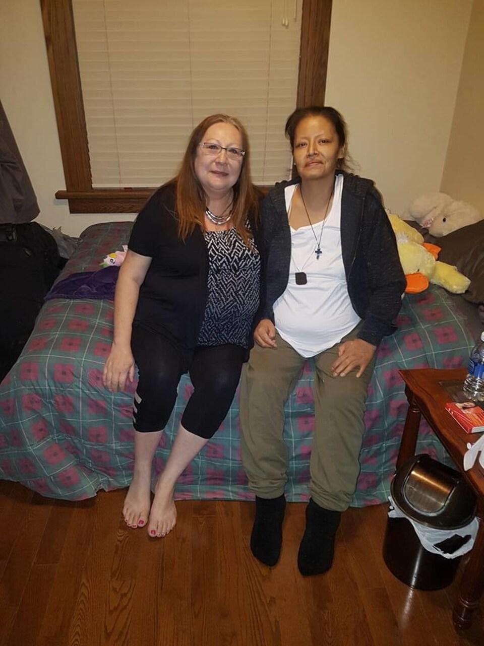 Les deux femmes posent collées, assises sur un lit dans un chambre