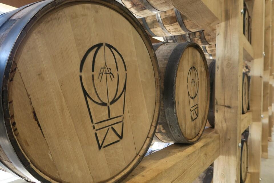 Des barils sont disposés à l'horizontal sur une grande étagère de bois.
