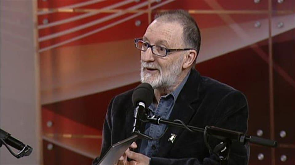 Jean-Claude Basque parle au micro, dans le studio de Radio-Canada-Acadie.