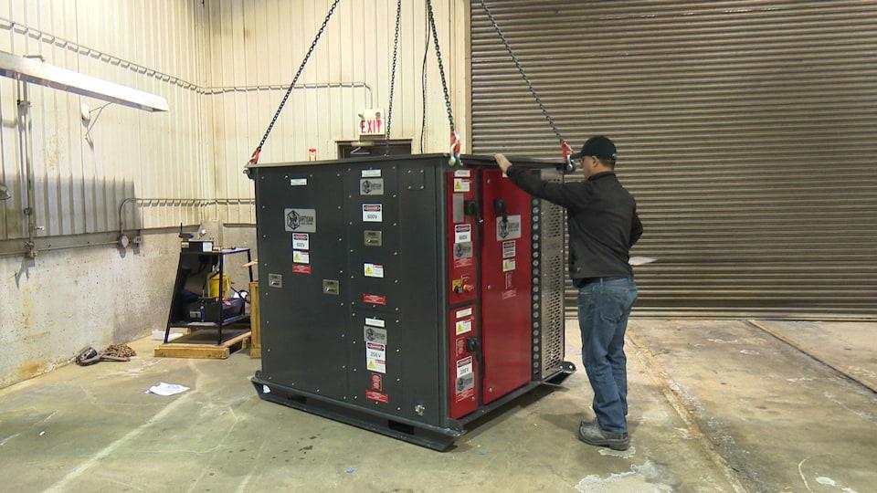 Mike Mayhew touche une batterie aussi grande que lui, suspendue par des chaînes, dans un garage.