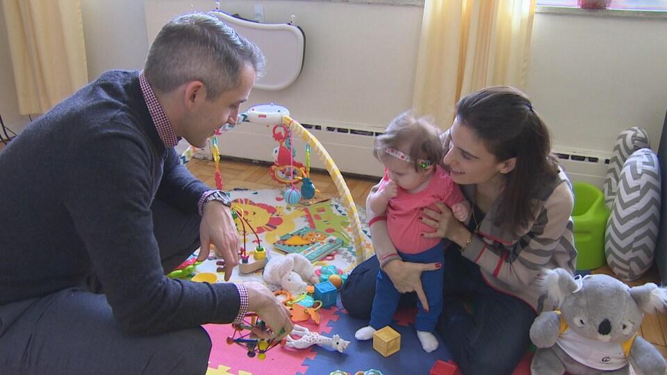 Une petite fille dans sa salle de jeux avec ses parents accroupis autour d'elle. On peut voir plusieurs jouets par terre autour d'eux.