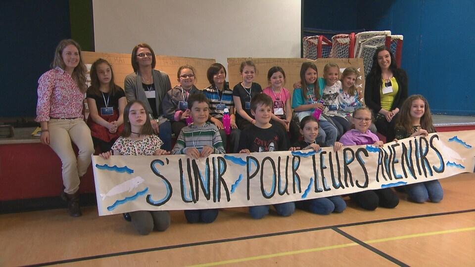 Des jeunes sont assis sur le sol et tiennent une affiche où il est écrit : S'unir pour leurs avenirs.