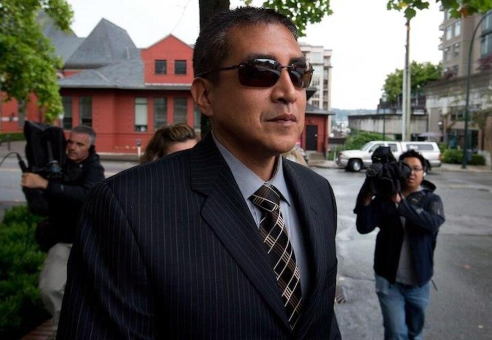Un homme en complet avec des lunettes fumées avec en arrière-plan des hommes qui portent des caméras vidéo