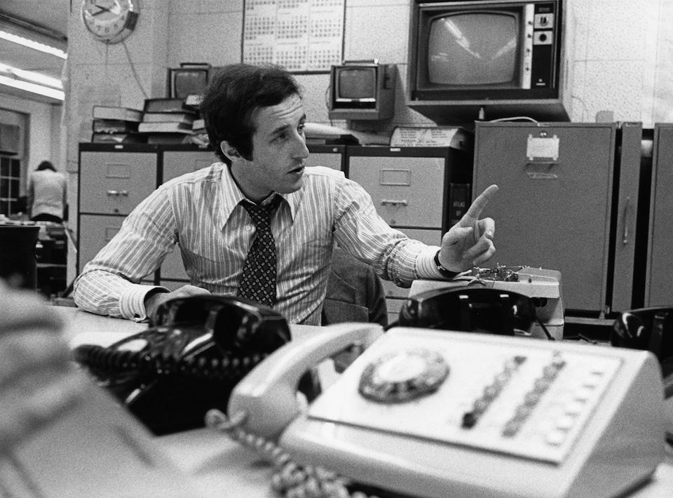 Dans une salle de nouvelles, l'animateur Bernard Derome, est assis à un bureau sur lequel il y a plusieurs appareils de téléphone. À l'arrière-plan, on voit des classeurs appuyés au mur où des téléviseurs sont accrochés.