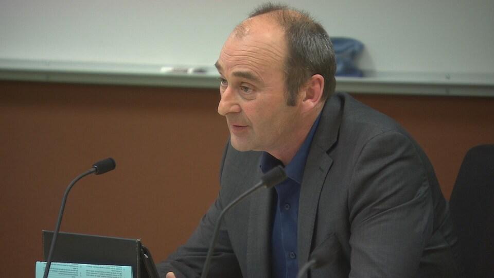 Le président de la CSFM Bernard Lesage, assis dans une salle lors d'une réunion. Il parle au micro.
