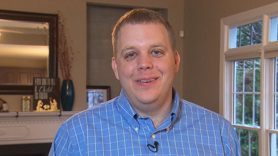 Un homme aux yeux bleus et portant une chemise sourit à la caméra.