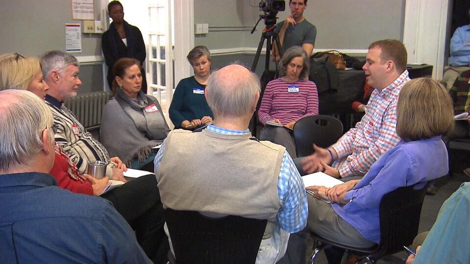 Des hommes et des femmes assis sur des chaises discutent en cercle dans un local sous le regard d'observateurs dont un caméraman.