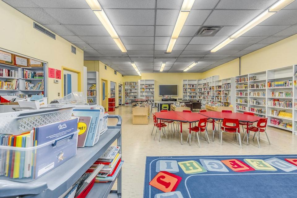 Une bibliothèque jaune, avec des tables basses, des étagères sur tous les murs.