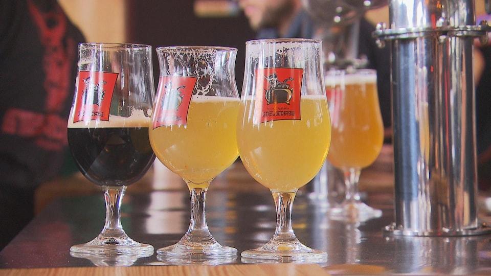 Des verres portant le logo de la microbrasserie Le Trou du diable et contenant de la bière sont disposés sur un comptoir.