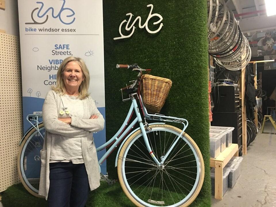 Une femme souriante se tient devant un vieux vélo bleu poudre dans un atelier de réparation de bicyclettes.