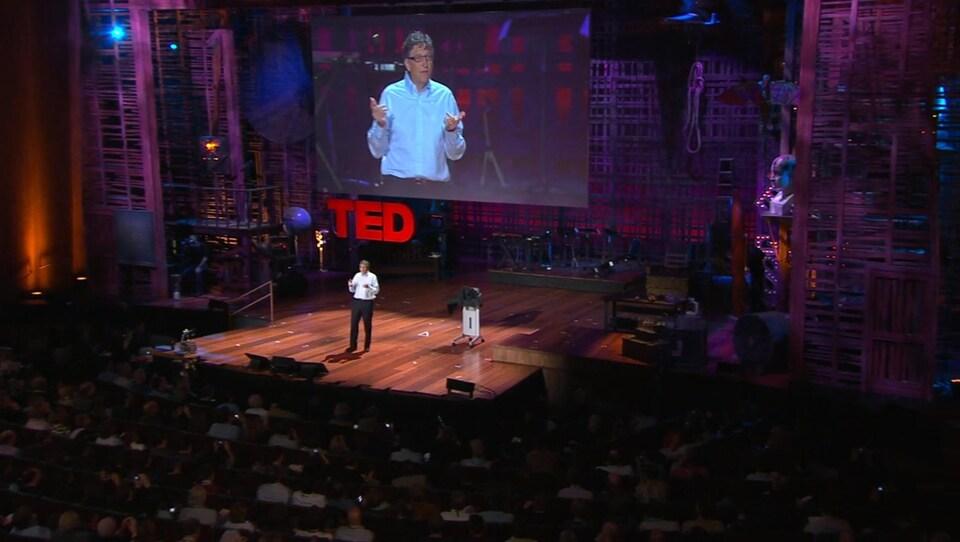 Bill Gates parle au public sur une grande scène.