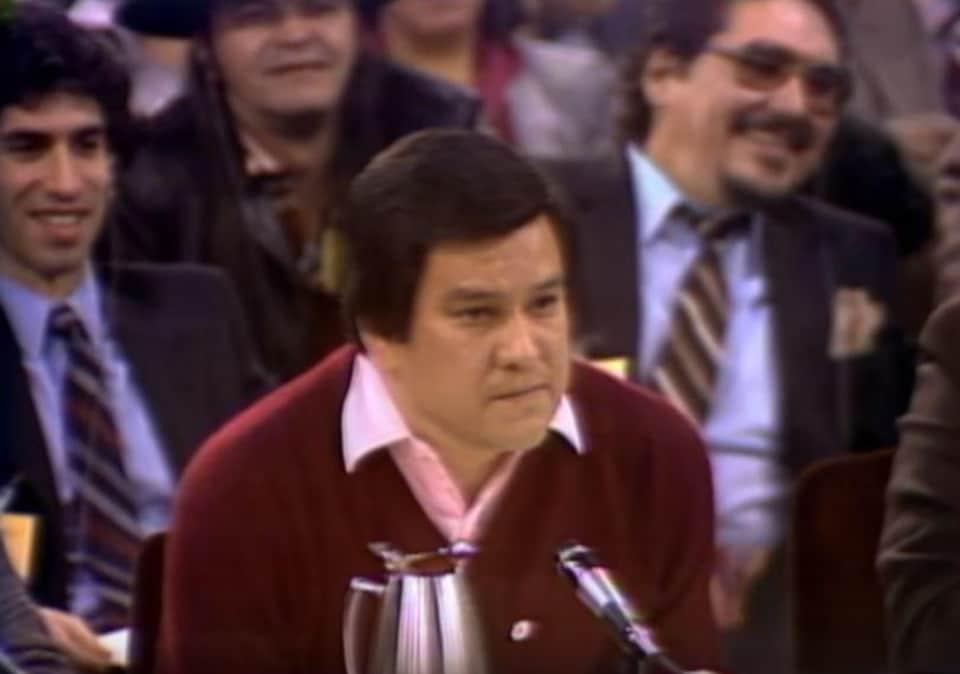 Un homme autochtone à l'air sérieux est devant des hommes blancs qui sourient.