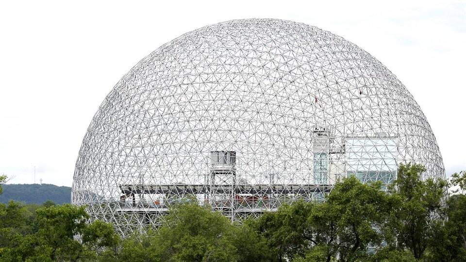 Une photo de la Biosphère de Montréal avec le mont Royal en arrière-plan.