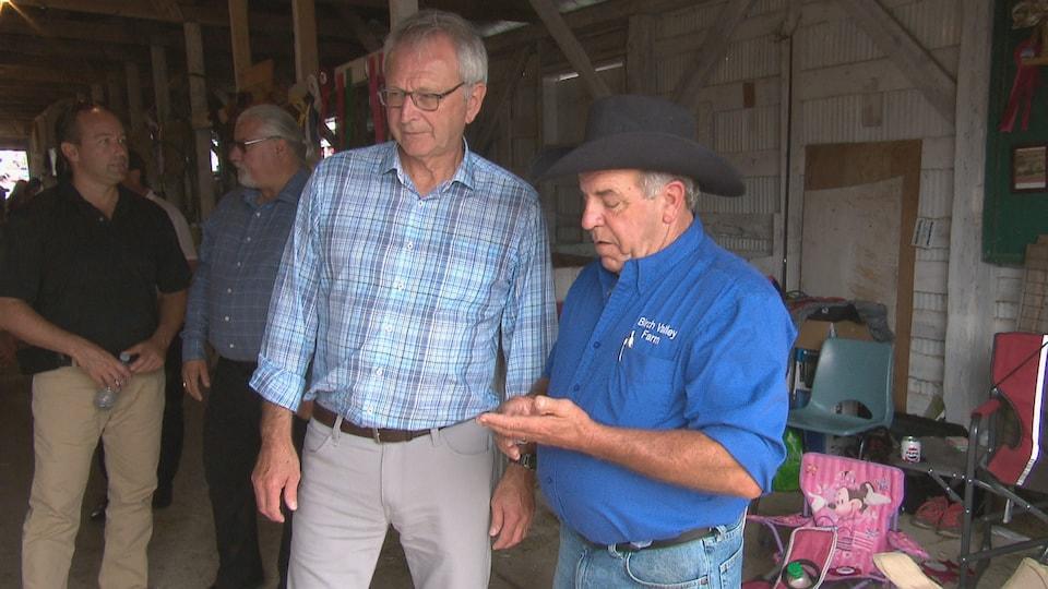 Blaine Higgs visite une étable avec un homme portant un chapeau de cow-boy.