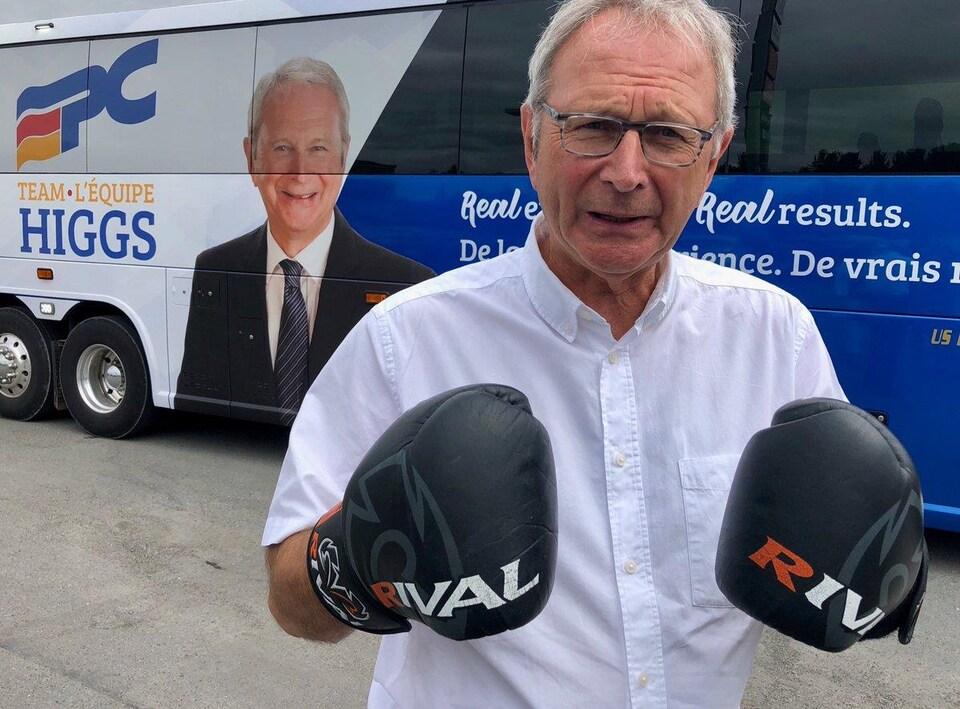 Le chef du Parti progressiste-conservateur avec des gants de boxe devant son autocar de campagne.