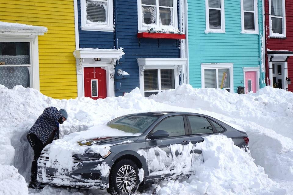Une femme déneige une automobile d'un banc de neige plus haut que le véhicule.