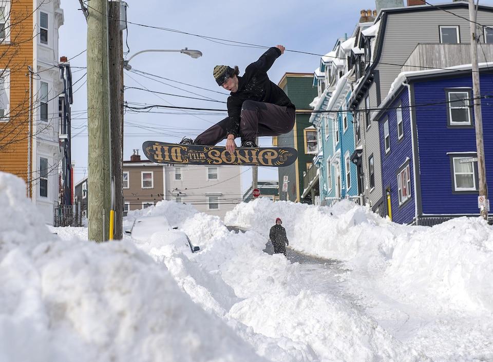 Un homme saute en planche à neige dans une rue après une tempête de neige.