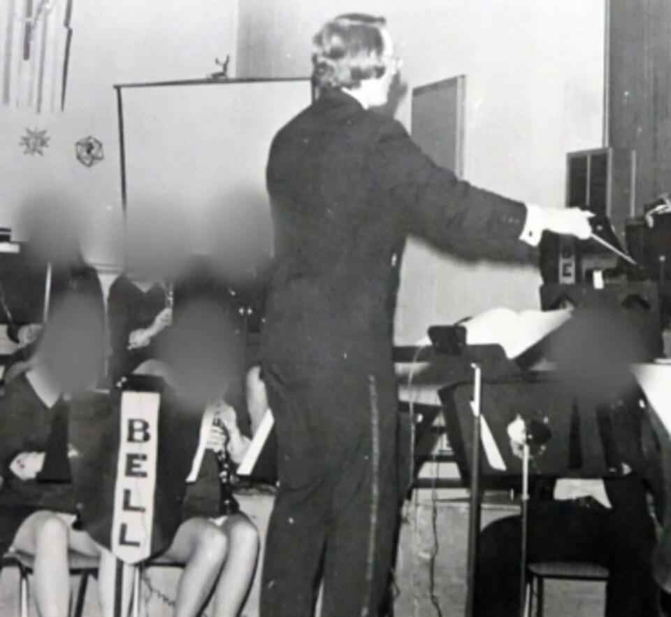Un homme vu de dos debout devant des élèves qui font de la musique.