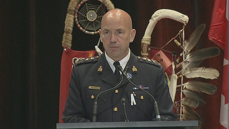 Un haut-dirigeant policier en uniforme s'adresse à une foule derrière un podium.