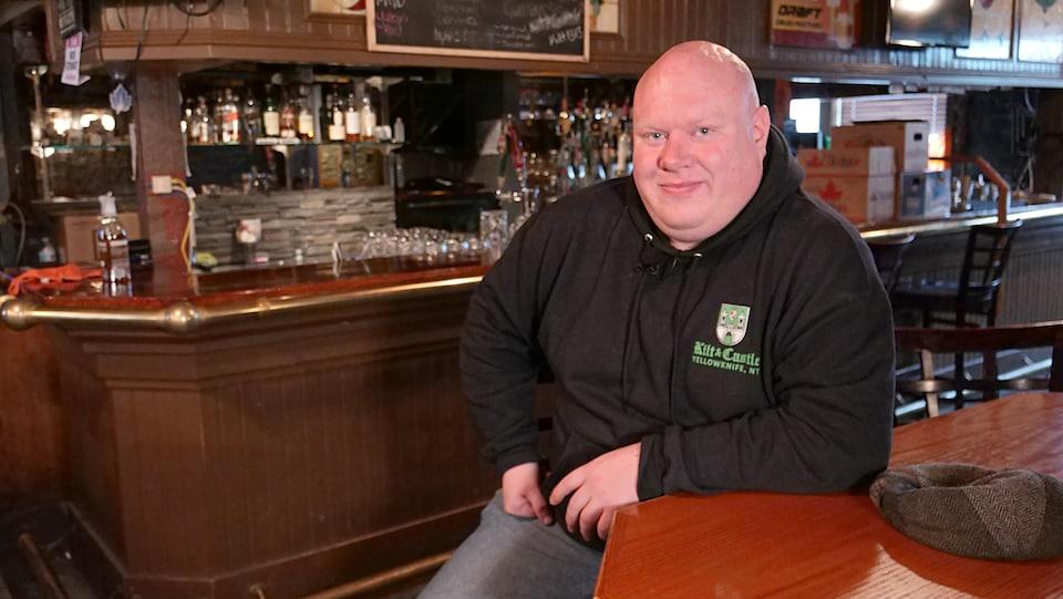 Un homme assis dans un pub sourit à la caméra.