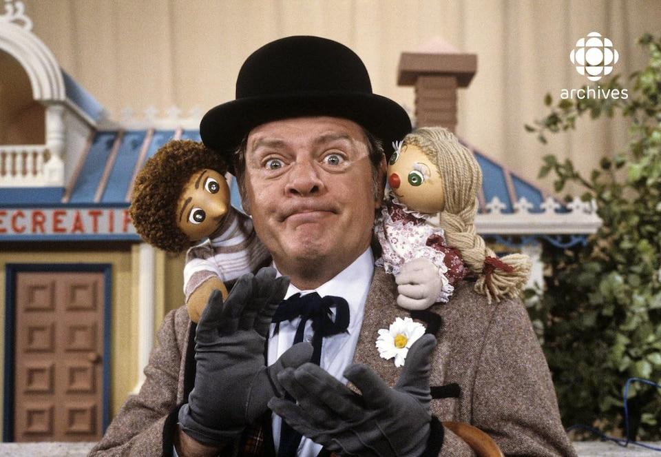 Les marionnette de Bobinette et Giovanni et le personnage de Bobino devant le décor du Centre récréatif de l'émission Bobino