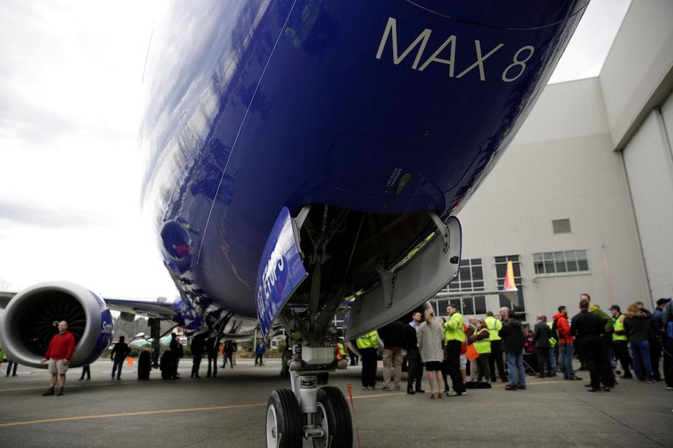 Des employés de Boeing devant un avion.