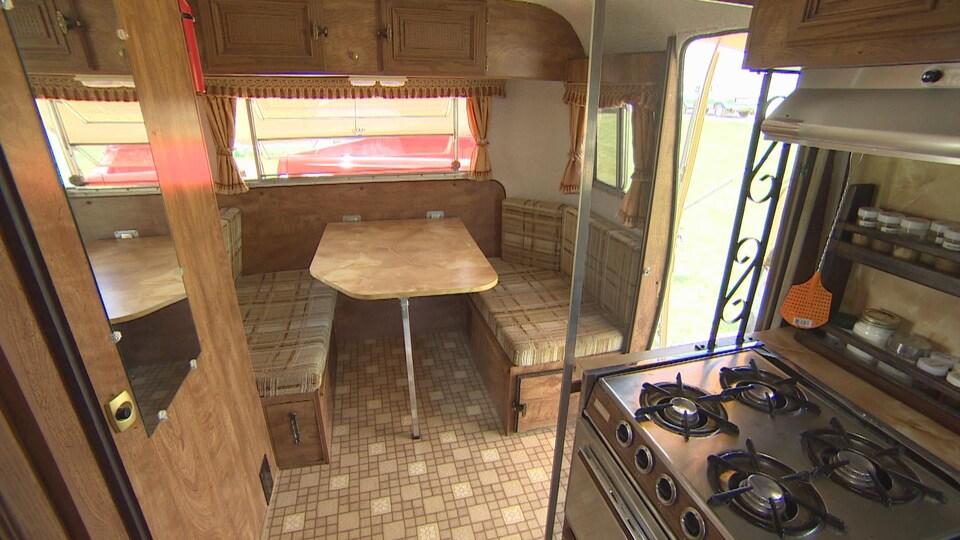 On voit que la caravane contient une table avec des bancs, une porte à gauche est celle des toilettes, et à droite se trouve la petite cuisine. Le tout est dans les tons bruns et dans le style de la fin des années soixante-dix.