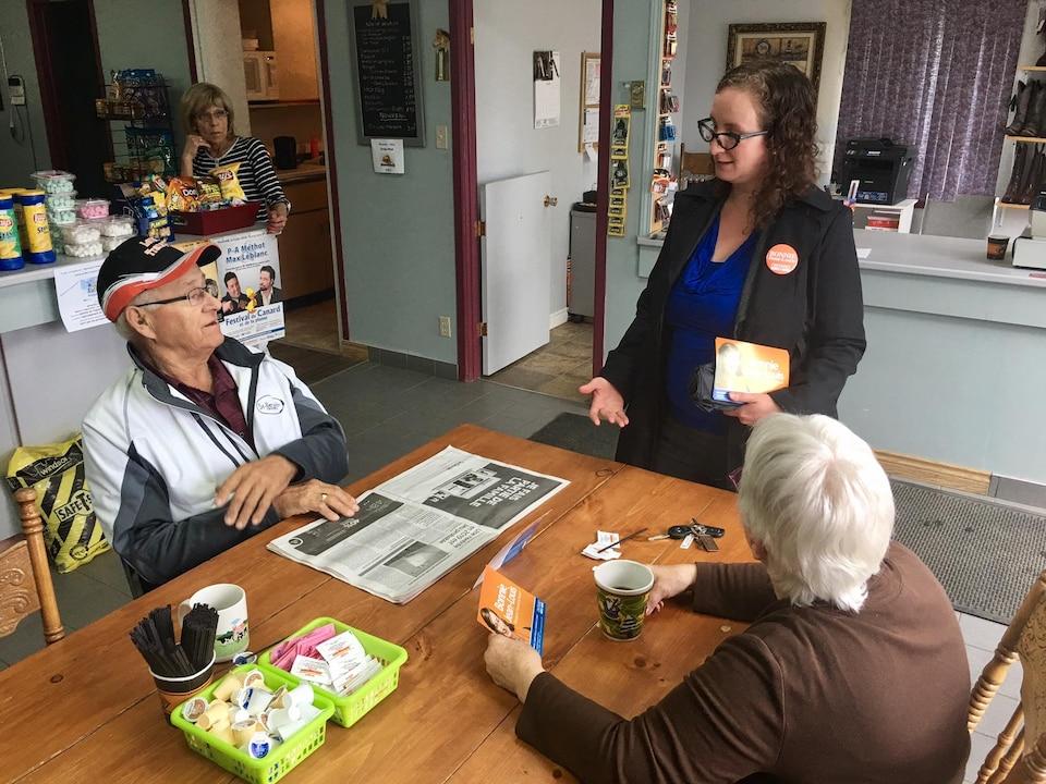 Une jeune femme debout discute avec deux personnes âgées assises à une table