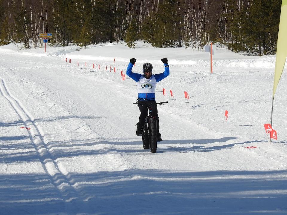 Un participant à la course de vélo à pneus surdimensionnés lève les bras alors qu'il s'apprête à franchir la ligne d'arrivée.