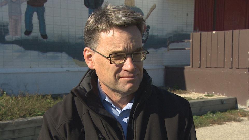 Un homme à lunettes, devant l'aréna de Saint-Vital, en entrevue avec Radio-Canada.