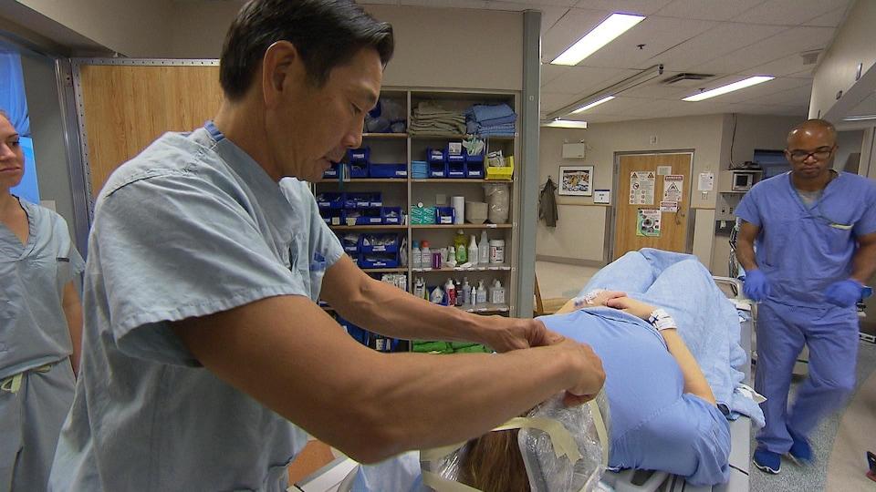 Le médecin est en train d'enlever les rubans adhésifs qui enserrent la tête de sa patiente.