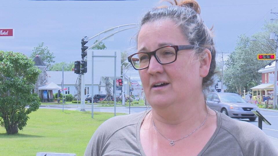 Une femme est dehors en bordure de route et se fait interviewer. Derrière elle, on voit un feu de signalisation et des voitures passer.
