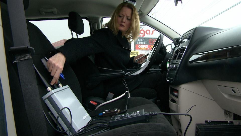 La journaliste Brigitte Bureau assise dans une voiture à côté d'un appareil pouvant déceler la présence d'intercepteurs d'IMSI.