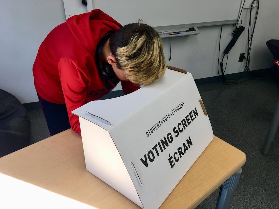 Une jeune graçon est debout, accoudé à une table. Devant lui, il y a une boite en carton avec l'inscription VOTING SCREEN ÉCRAN qui cache ce que le garçon écrit.